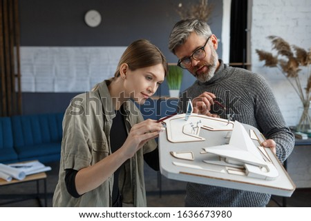 3d architects team working in office with building 3d model. Architects inspect building layout, planning construction project, searching new ideas. Partners discussing at work. Business concept.
