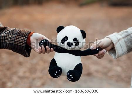 Girls hands holding panda on the autumn background. Panda toy. Panda doll black and white, black rim of eyes, panda toy for children