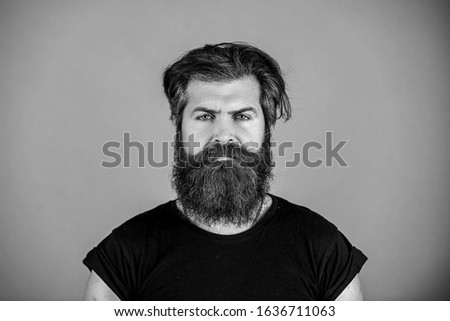 Long beard. Perfect beard. Close-up of young bearded man standing against blue background. #1636711063