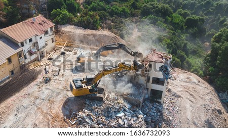 Urban Renewal‎. Urban Regeneration. Demolition of a building for new construction. Dismantling of a house. Excavator demolishing barracks for new construction project.  Royalty-Free Stock Photo #1636732093