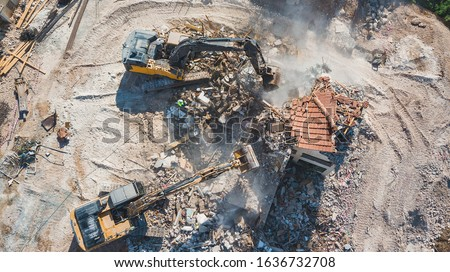 Urban Regeneration. Demolition of a building for new construction. Dismantling of a house. Excavator demolishing barracks for new construction project. Urban Renewal‎.  Royalty-Free Stock Photo #1636732708