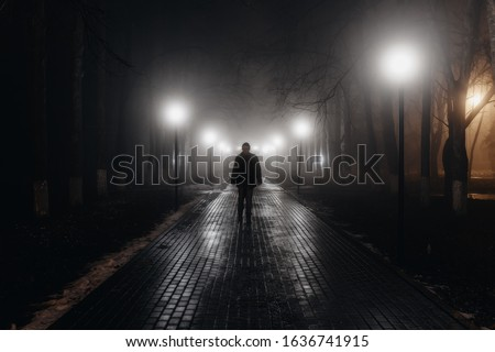 Sad man alone walking along the alley in night foggy park. Back view Royalty-Free Stock Photo #1636741915