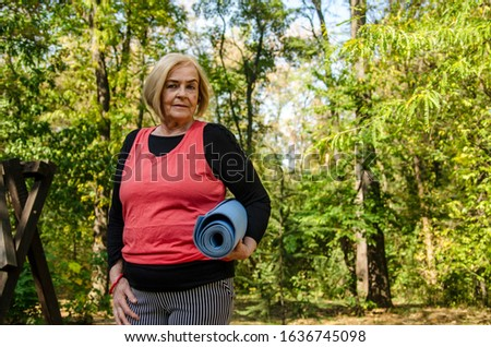Old senior woman with yoga mat outdoors in green woods going on training.Healthy lifestyle and exercise in retirement.Grey hair matured  female workout outdoors.Copy space #1636745098