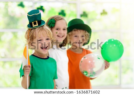 Family celebrating St. Patrick's Day. Irish holiday, culture and tradition. Kids wear green leprechaun hat and beard with Ireland flag and clover leaf. Children having fun at St Patrick party. Royalty-Free Stock Photo #1636871602