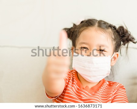 Coronavirus Covid-19.Online education.Little asian kid girl wearing face mask show thumbs up for Thank you doctor, Happy at home. Covid-19 coronavirus.Stay home.Social distancing.New normal behavior. #1636873171