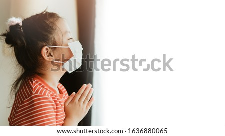 Little Chinese girl wearing mask for protect pm2.5 and coronavirus Covid-19.Stay at home praying to GOD.Online church worship in sunday.Little asian girl hand praying at home.Social distancing. #1636880065