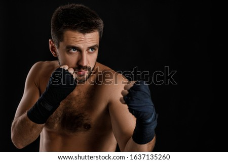 boxer man with bandage on hands training before fight and showing the different movements on black background #1637135260