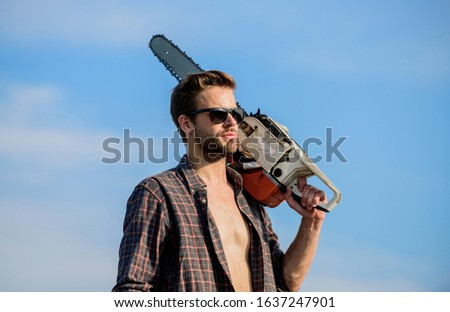 Gardener lumberjack equipment. Get stylish haircut. Barbershop concept. Masculinity concept. Handsome man with chainsaw blue sky background. Dangerous job. Powerful chainsaw. Lumberjack hold chainsaw. #1637247901