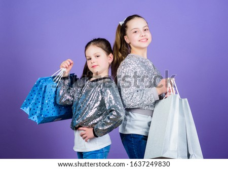 Shopping and purchase. Black friday. Sale and discount. Shopping day. Children bunch packages. Kids fashion. Girls sisters friends with shopping bags violet background. Because image is everything.