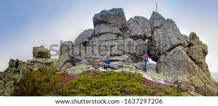 Southern Urals. A mature tourist makes an ascent to the top along a large stone placer. #1637297206