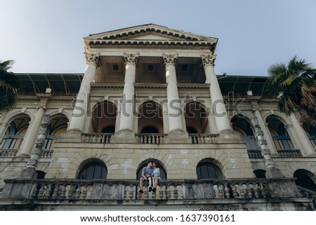 A young European couple sits amid an abandoned Stalin-style empire-style hotel. #1637390161