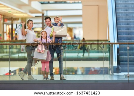Parents and two kids waving shopping bags at shopping mall #1637431420