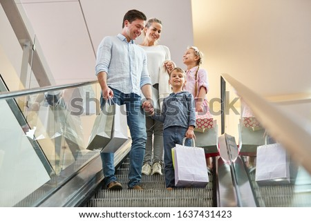 Parents and two children on an escalator with shopping bags in the shopping center #1637431423