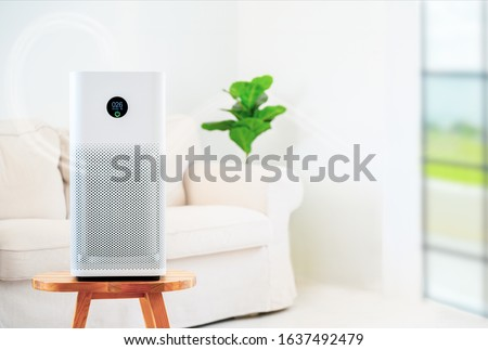 air purifier a living room,  air cleaner removing fine dust in house. protect PM 2.5 dust and air pollution concept Royalty-Free Stock Photo #1637492479