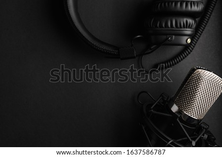 Studio black studio microphone with studio headphones on a black background. Banner. Radio, work with sound, podcasts. #1637586787