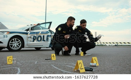 Two police officers colleagues examine illegal drugs as evidence squatting near the police car. Investigation area.