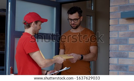 Young delivery man knocking on customer door holding mail letters. Attractive cheerful man coming up signing up on paper taking his parcel. Post delivery services.