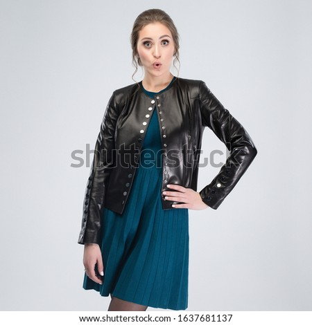 Beautiful emotional woman in the black leather jacket and dark turquoise dress at the studio with light gray background. Copy space for your design. Concept with emotions #1637681137