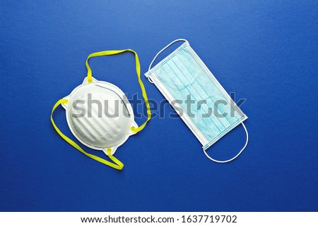 Two types of protective face masks on blue background. Protective masks as precaution in spread of coronavirus 2019-nCoV, Wuhan virus, flat lay Royalty-Free Stock Photo #1637719702