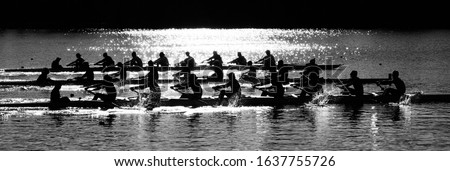 The morning sun behind college rowers competing on Lake Carnegie in Princeton, NJ Royalty-Free Stock Photo #1637755726