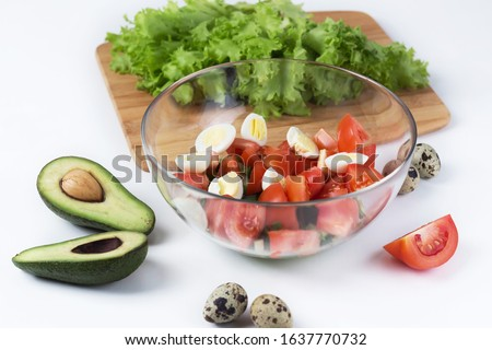fresh vegetable salad with avacado and quail egg in a glass transparent plate on a white table, next to greens. healthy nutrition, proper nutrition #1637770732