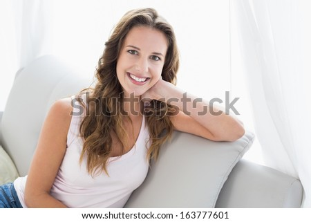 Portrait of a smiling young woman sitting on sofa in living room at home #163777601