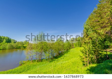 The lake is a large body of water surrounded by land. Walnut and pine trees grow along the edge, complete calm, beautiful hatching in the water #1637868973