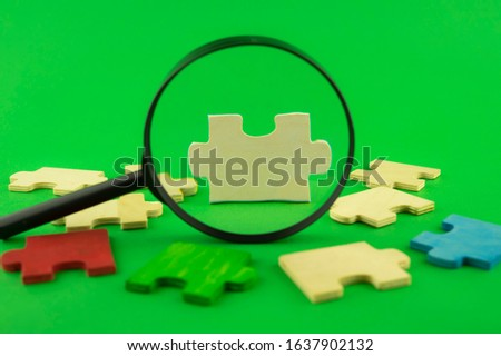 Colorful jigsaw puzzle pieces with magnifying glass focused on a single white corner piece in a conceptual image over green for search, investigation and problem solving #1637902132