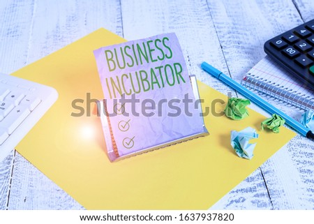 Handwriting text Business Incubator. Concept meaning company that helps new and startup companies to develop Notepaper stand on buffer wire in between computer keyboard and math sheets. #1637937820