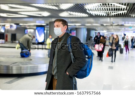 Young European man in gray coat, protective disposable medical mask in airport. Afraid of dangerous N-CoV 2019 influenza coronavirus mutated and spreading in China. Blue backpack, suitcase on wheels. #1637957566