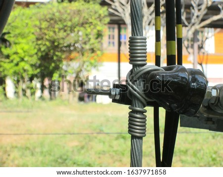 Closeup of insulators and cables. Fixing of cables to insulators with wire On a green tree background with a copying area .Selective focus #1637971858