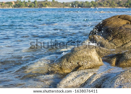 outdoor reservoir wavy water surface rocky shore line scenic view with stones texture and fuzzy motion of drop splash foreground, main land waterfront background  #1638076411