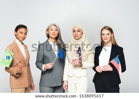 multicultural women with flags of different countries isolated on white
