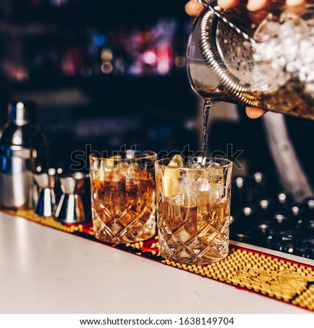 Bartender pouring whiskey drink into whiskey glasses on the bar #1638149704