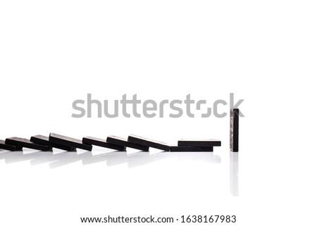Falling black dominoes on white background. Domino effect.  #1638167983