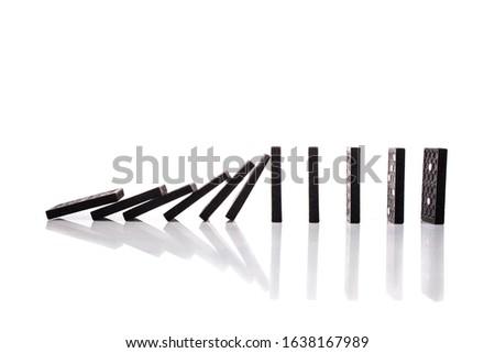 Falling black dominoes on white background. Domino effect.  #1638167989
