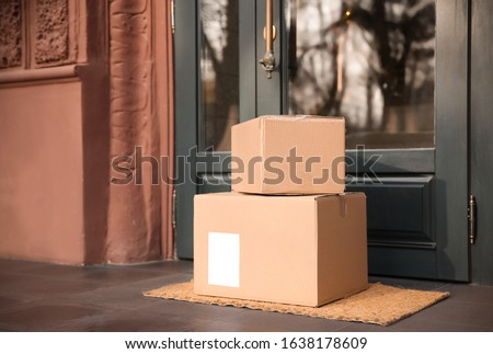 Delivered parcels on door mat near entrance #1638178609