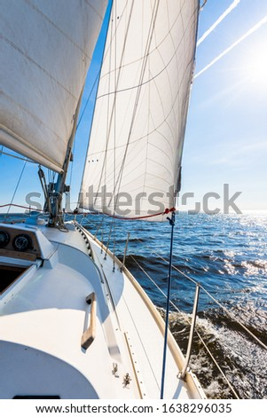 White sloop rigged yacht sailing in an open Baltic sea on a clear sunny day. A view from the deck to the bow, mast and sails. Estonia #1638296035