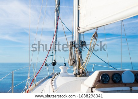 White sloop rigged yacht sailing in an open Baltic sea on a clear sunny day. A view from the deck to the bow, mast and sails. Estonia #1638296041