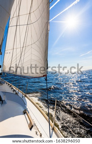 White sloop rigged yacht sailing in an open Baltic sea on a clear sunny day. A view from the deck to the bow, mast and sails. Estonia #1638296050