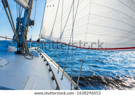White sloop rigged yacht sailing in an open Baltic sea on a clear sunny day. A view from the deck to the bow, mast and sails. Estonia #1638296053