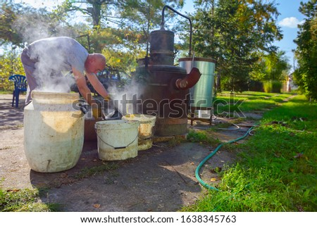 Man is unloading boiler of homemade distillery made of copper to release used fruit marc, making moonshine schnapps, alcoholic beverages such as brandy, cognac, whiskey, bourbon, gin, and scotch. #1638345763