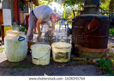 Man is unloading boiler of homemade distillery made of copper to release used fruit marc, making moonshine schnapps, alcoholic beverages such as brandy, cognac, whiskey, bourbon, gin, and scotch. #1638345766