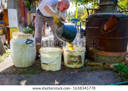 Man is unloading boiler of homemade distillery made of copper to release used fruit marc, making moonshine schnapps, alcoholic beverages such as brandy, cognac, whiskey, bourbon, gin, and scotch. #1638345778