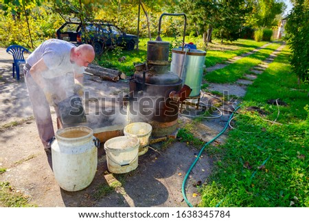 Man is unloading boiler of homemade distillery made of copper to release used fruit marc, making moonshine schnapps, alcoholic beverages such as brandy, cognac, whiskey, bourbon, gin, and scotch. #1638345784