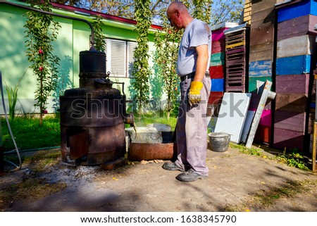 Man is unloading boiler of homemade distillery made of copper to release used fruit marc, making moonshine schnapps, alcoholic beverages such as brandy, cognac, whiskey, bourbon, gin, and scotch. #1638345790