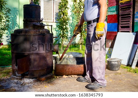 Man is unloading boiler of homemade distillery made of copper to release used fruit marc, making moonshine schnapps, alcoholic beverages such as brandy, cognac, whiskey, bourbon, gin, and scotch. #1638345793
