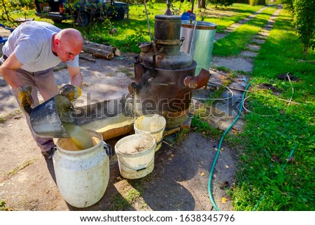 Man is unloading boiler of homemade distillery made of copper to release used fruit marc, making moonshine schnapps, alcoholic beverages such as brandy, cognac, whiskey, bourbon, gin, and scotch. #1638345796