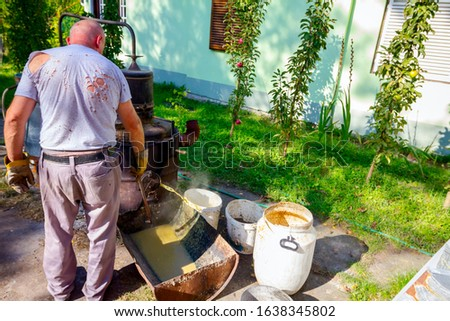 Man is unloading boiler of homemade distillery made of copper to release used fruit marc, making moonshine schnapps, alcoholic beverages such as brandy, cognac, whiskey, bourbon, gin, and scotch. #1638345802