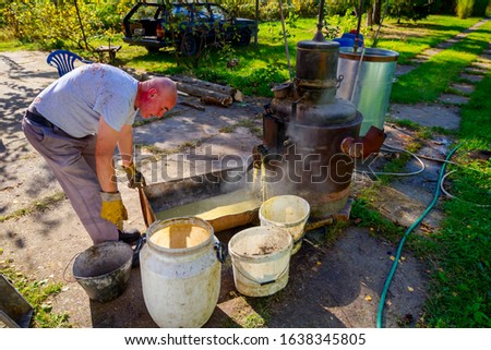Man is unloading boiler of homemade distillery made of copper to release used fruit marc, making moonshine schnapps, alcoholic beverages such as brandy, cognac, whiskey, bourbon, gin, and scotch. #1638345805
